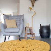 gehaakt geel vloerkleed bij fauteuil